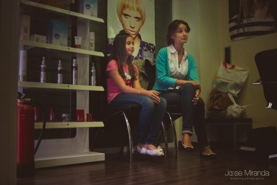 La novia y su sobrina en la peluquería mientras ven a su hermana como terminan de peinarla