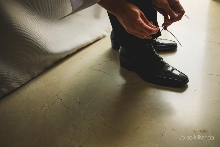 detalle de las manos del novio atándose los zapatos en una fotografia de boda de Jose Miranda en Linares