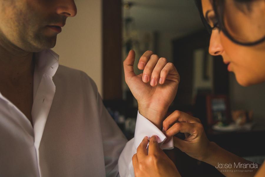 detalle de los puños del novio mientras se los arregla su hermana en una fotografia de boda de Jose Miranda