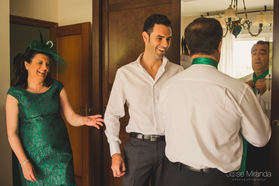 Antonio el novio ayudando a su padre a ponerse la corbata mientras se mira en el espejo y su madre se ríe en una boda en Linares