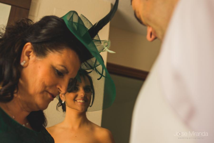 madre del novio arreglando los puños del novio mientras su hermana lo mira expectante con cara emocionada en una boda en Linares