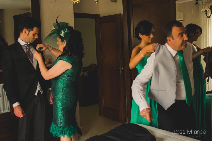 Madre arreglando la flor del chaqué del novio y su hermana ayudando a su padre en boda linares de jose miranda fotografia