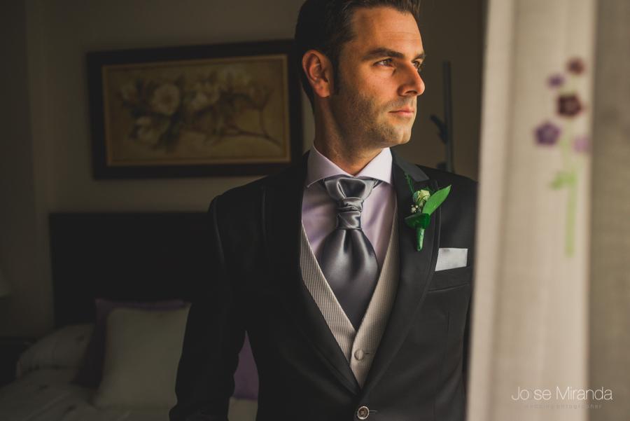 Retrato de novio mientras mira por una ventana como llegan los invitados a la boda en Linares Fotografia de Boda de Jose Miranda