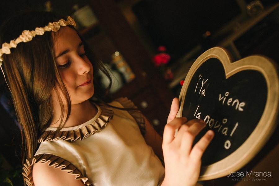 niña de arras de boda con pizarra de corazón y mensaje ya viene la novia