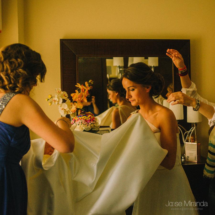 momento de la boda en el que la novia se está poniendo el vestido y hermanas ayudándole