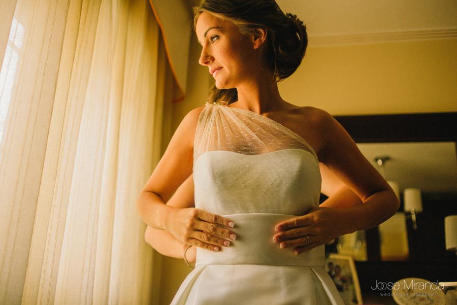 Fotografía de novia delante de la ventana vistiéndose el día de su boda con moño bajo