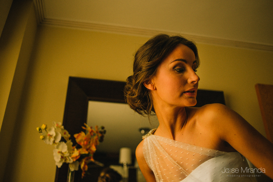 fotografía de novia delante del espejo con maquillaje sencillo y vestido con hombro descubierto