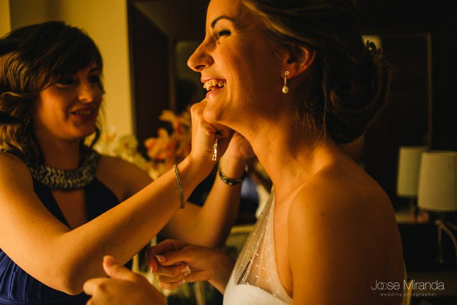 hermana colocándole el pendiente a una novia mientras sonrien