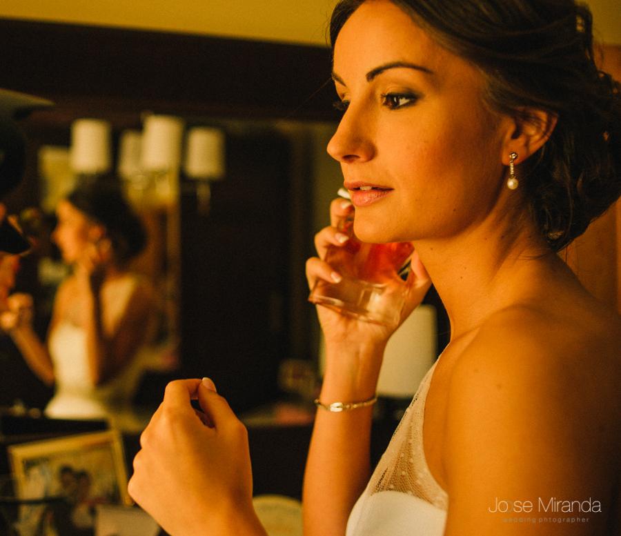 fotografia de novia poniéndose perfume con pendientes de perlas y maquillaje suave