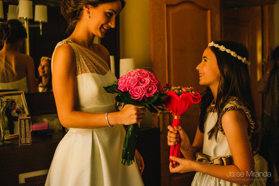 niña de arras y novia con ramos. niña de arras con ramo de chupa chups y novia con ramo de rosas rosa