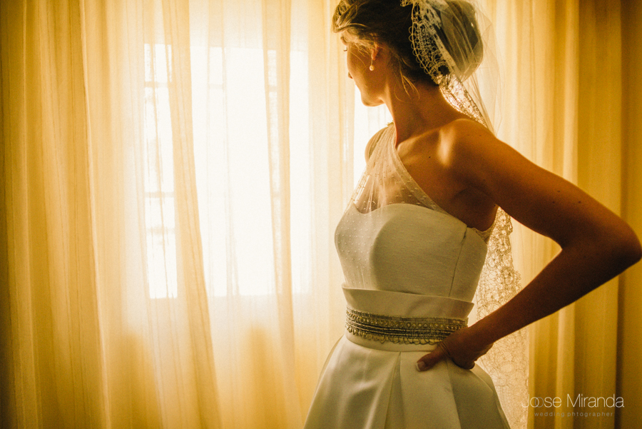novia entre cortinas con moño bajo y velo con puntilla