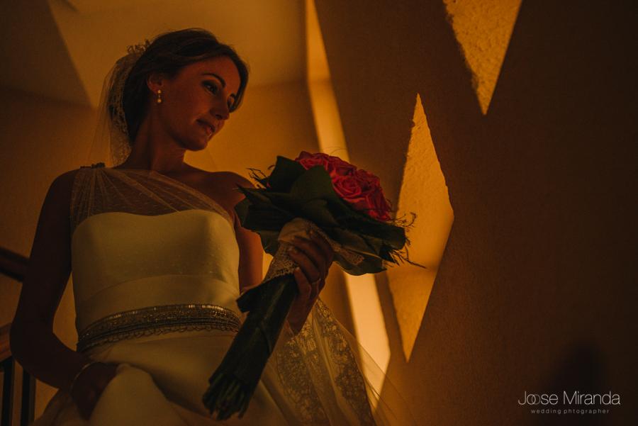 Retrato de novia con una luz tenue bajando las escaleras de su casa con el ramo de novia en un boda en Linares en una fotografia de Jose Miranda