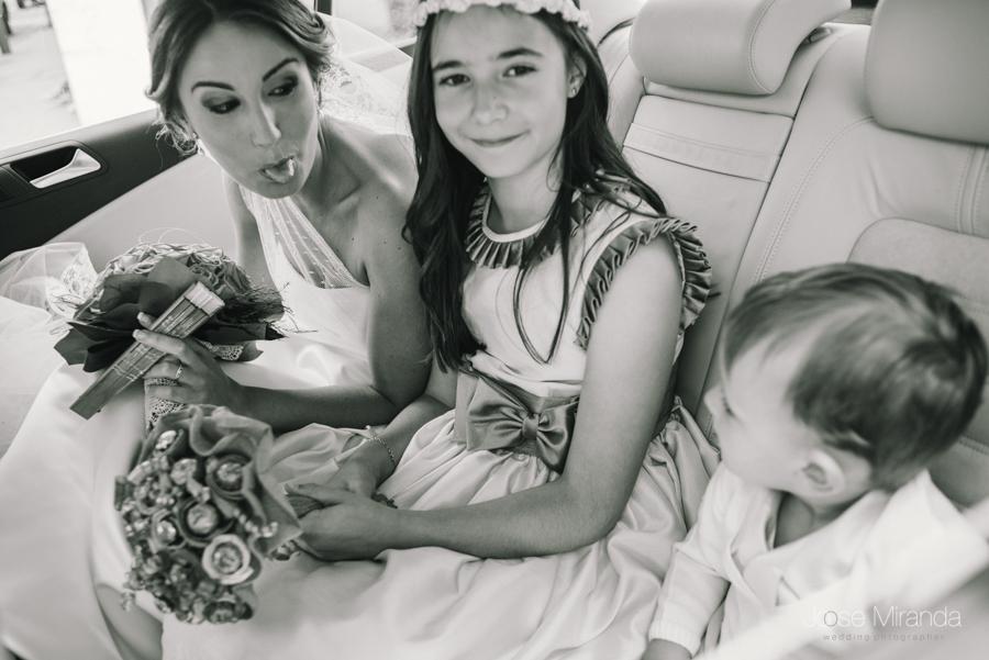 Novia montada en el coche de boda sacandole la lengua a los niños de arras en una boda en Linares