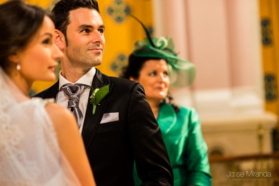 Los novios y la madrina observando como toca el coro en el Hospital de los Marqueses de Linares  en una fotografía de boda de Jose Miranda