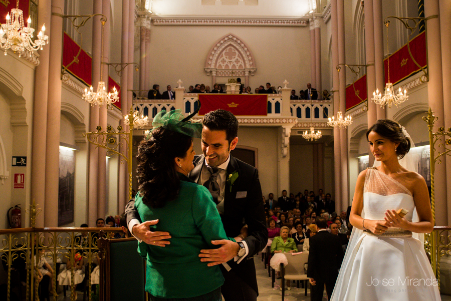 Novio abrazando a su madrina mientras mira la novia con el coro, las columnas y las lamparas del Hospital de los Marqueses de Linares al fondo en una fotografia de boda de Jose Miranda