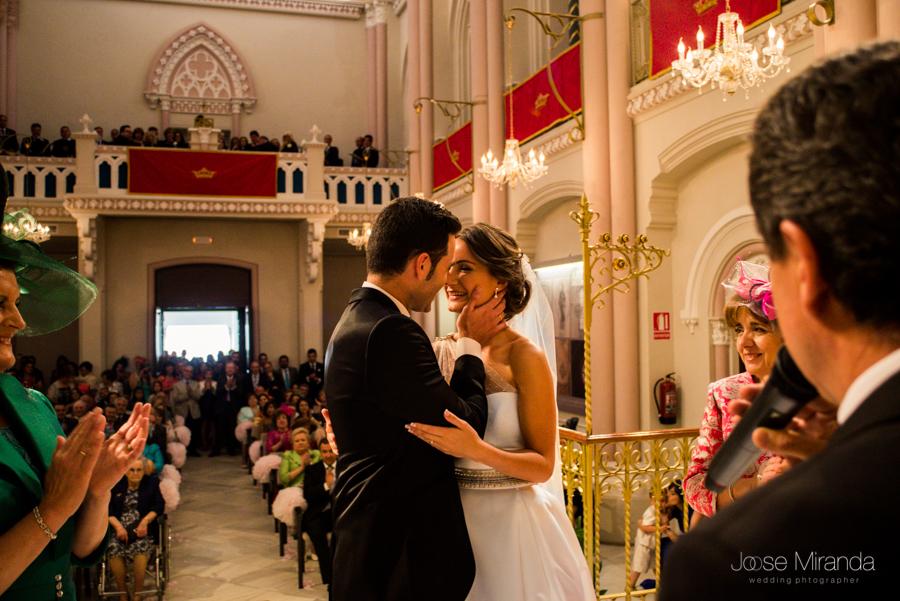 Beso de los novios ante la atenta mirada de las madrinas en la celebración civil en el Hospital de los Marqueses de Linares