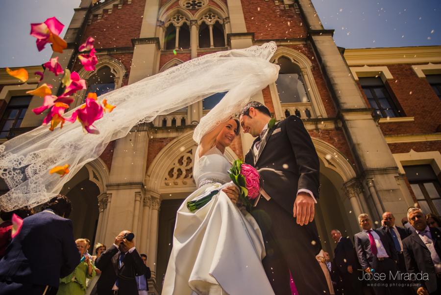 La novia extendiendo el velo para tapar al novio mientras los invitados les tiran arroz y pétalos de rosas delante del Hospital de los Marqueses de Linares