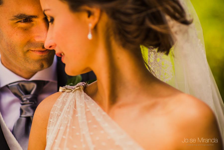 retrato del novio con la novia desenfocada mientras se tocan frente con frente en los campos de Linares en una fotografía de boda de Jose Miranda en Jaén