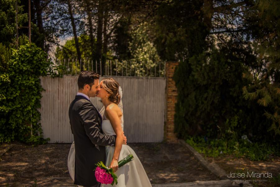 novios besándose ante una puerta y los arboles de los campos de linares en una fotografía de Jose Miranda