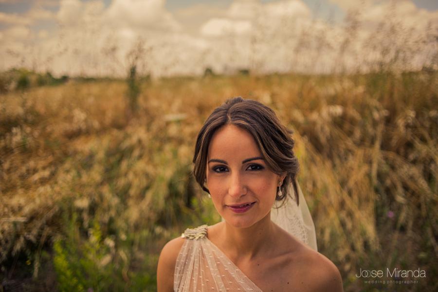 retrato de novia sonriendo con los campos de linares desenfocados al fondo y el cielo con nubes en una fotografía boda de Jose Miranda