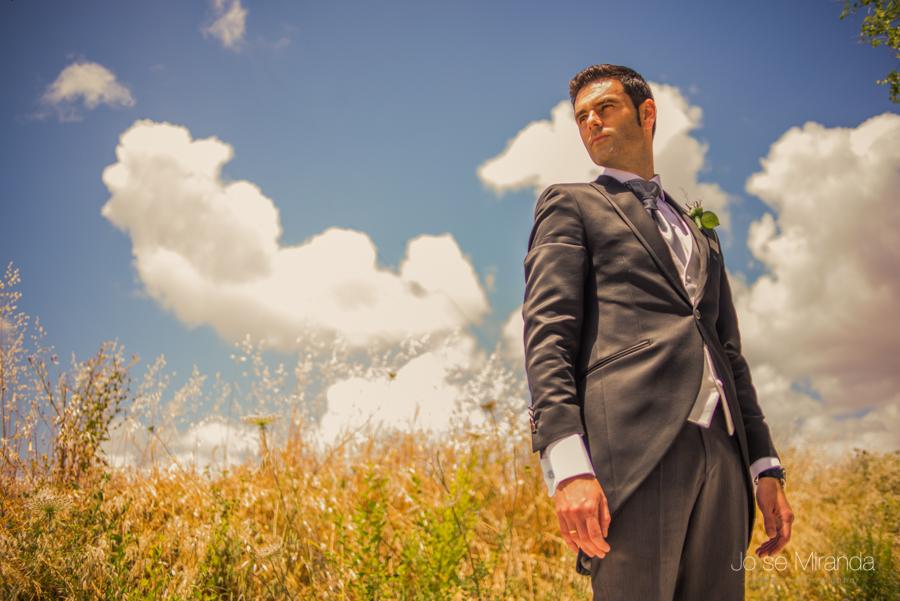 Retrato de novio imponente con el cielo y las nubes al fondo en el campo de Linares