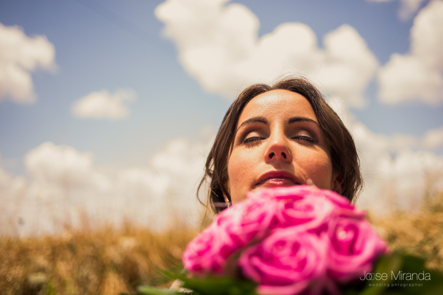 Retrato de novia con su ramo de rosas rosas desenfocado y la nubes de algodón y el cielo azul de Linares en una fotografía de boda de Jose Miranda
