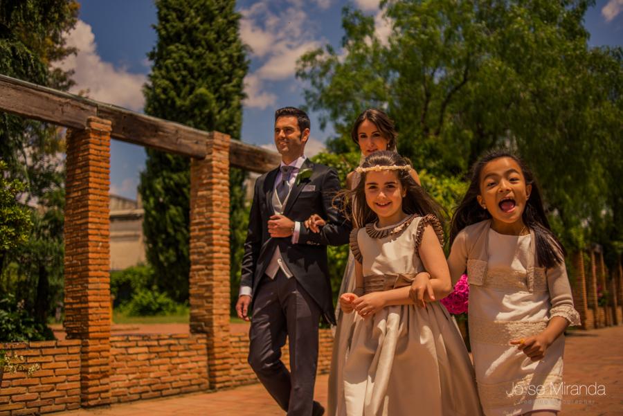 Novios entrando en La Hacienda El Campero desenfocados y unas niñas riendo delante de ellos y al mismo paso en una fotografía de boda en Linares de Jose Miranda