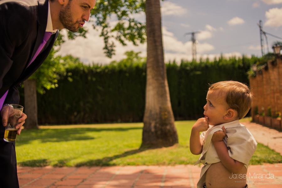 Niño de arras comiendose un chupachups mientras mira a su padre que le hace carantoñas en la Hacienda El Campero de Linares