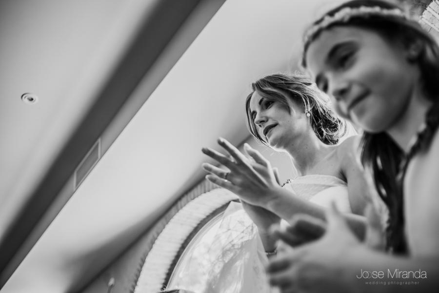 La novia mira emocionada como le canta el novio mientras da palmadas con la niña de arras en primer plano en la Hacienda El Campero de Linares