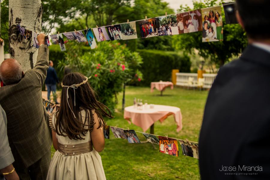 Niña de arras viendo las fotografías colgadas entre los arboles de la Hacienda el Campero de Linares
