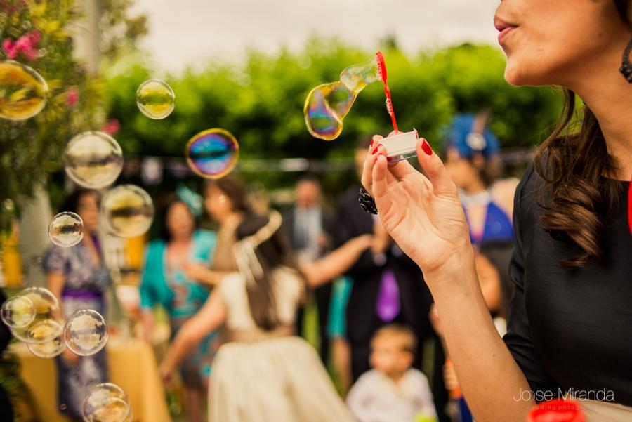 Detalle de invitada jugando con pompas de jabón durante el baile de la boda en la Hacienda el Campero de Linares