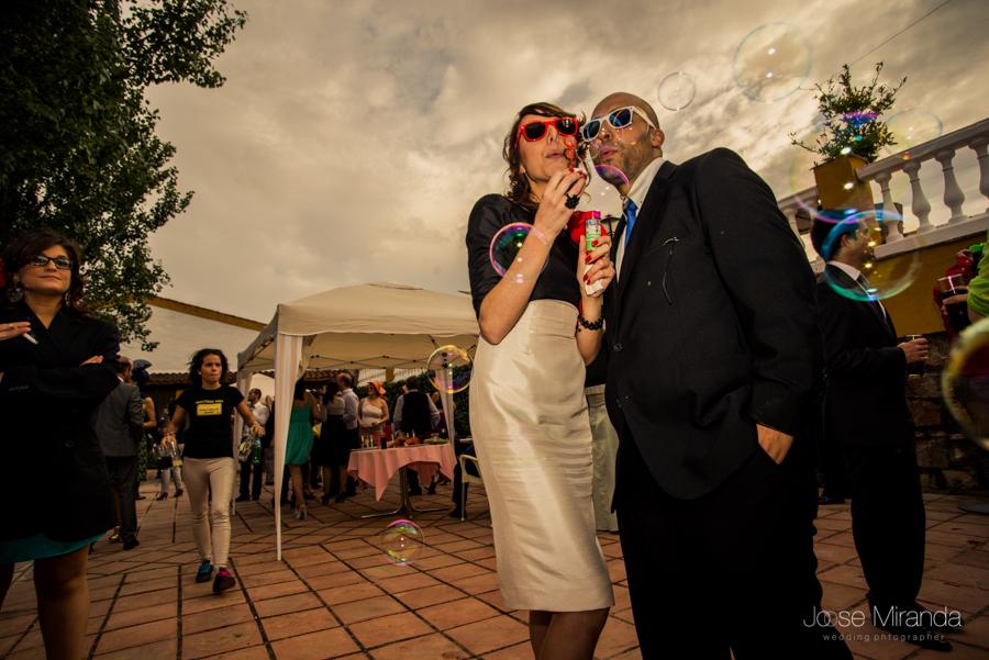 Invitados de boda con gafas de juguete jugando con pompas de jabón en la Hacienda el Campero de Linares