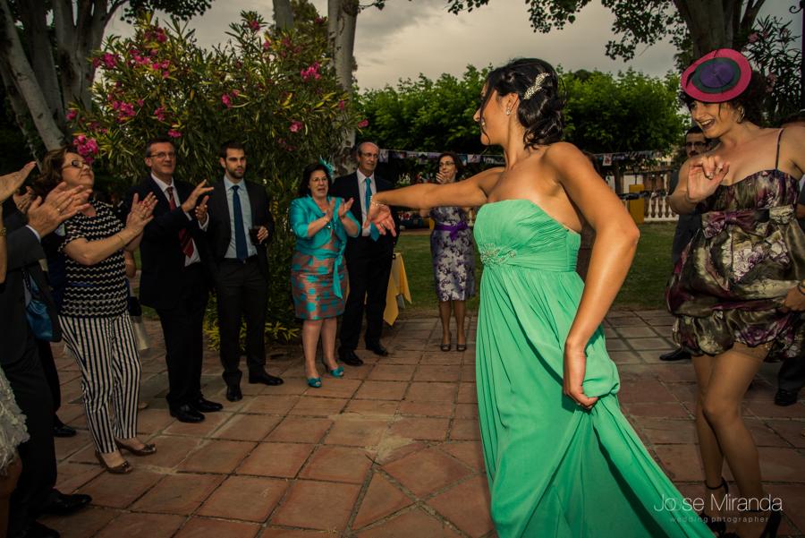 Hermana del novio bailando sevillanas con con los invitados de la boda en el Jardín de la Hacienda El Campero de Lnares