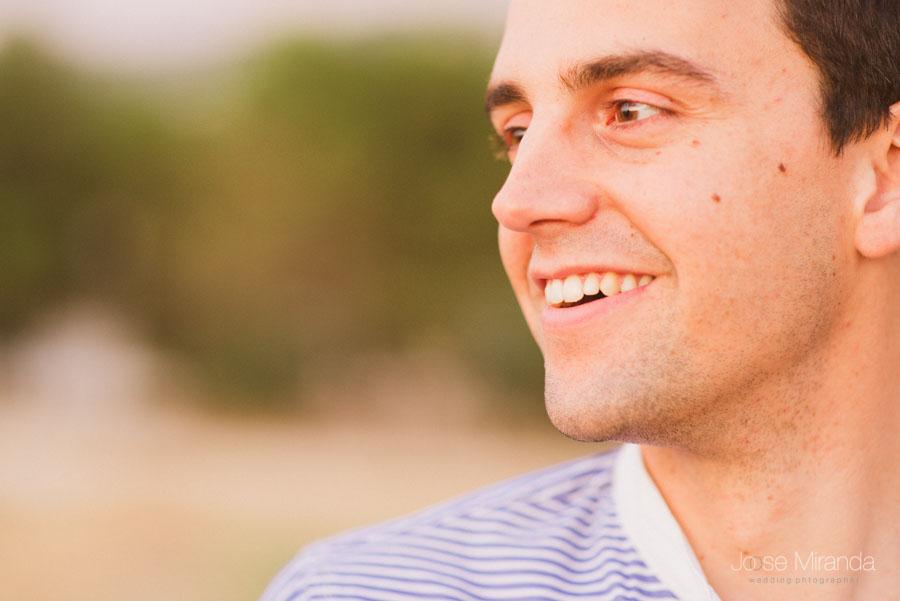 novio sonriendo y mirando ilusionadamente a su novia en una sesión de pre-boda en los campos de Jaén por Jose Miranda