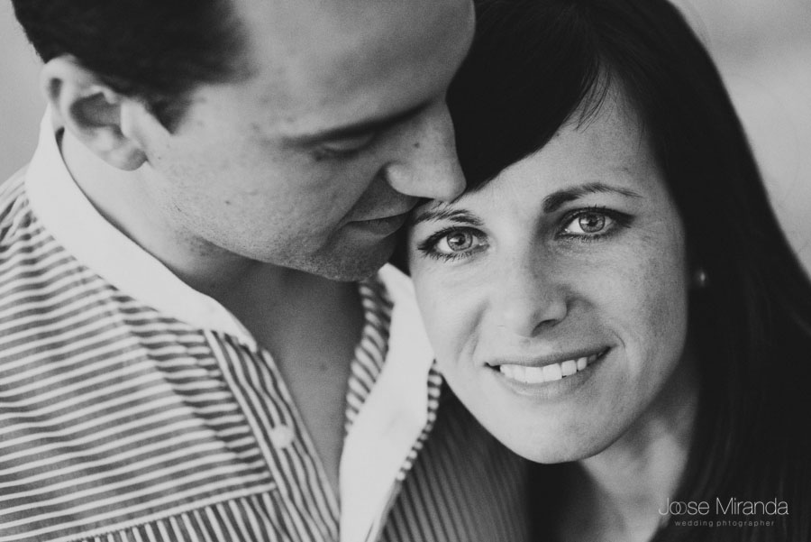 retrato en blanco y negro de un novio besando a la novia mientras ella mira a camara