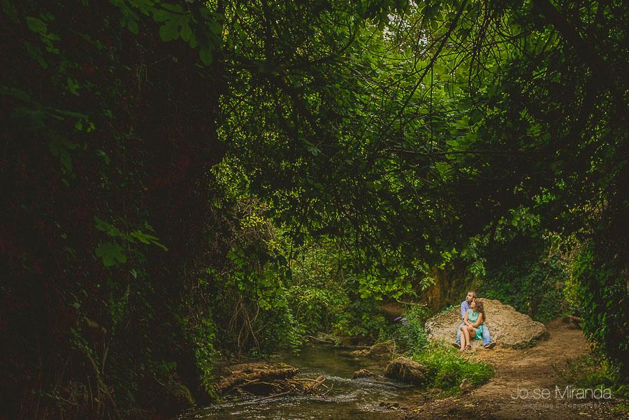 Novios abrazados sobre una piedra del rio y un claro del bosque fotografia de Jose Miranda en Jaén