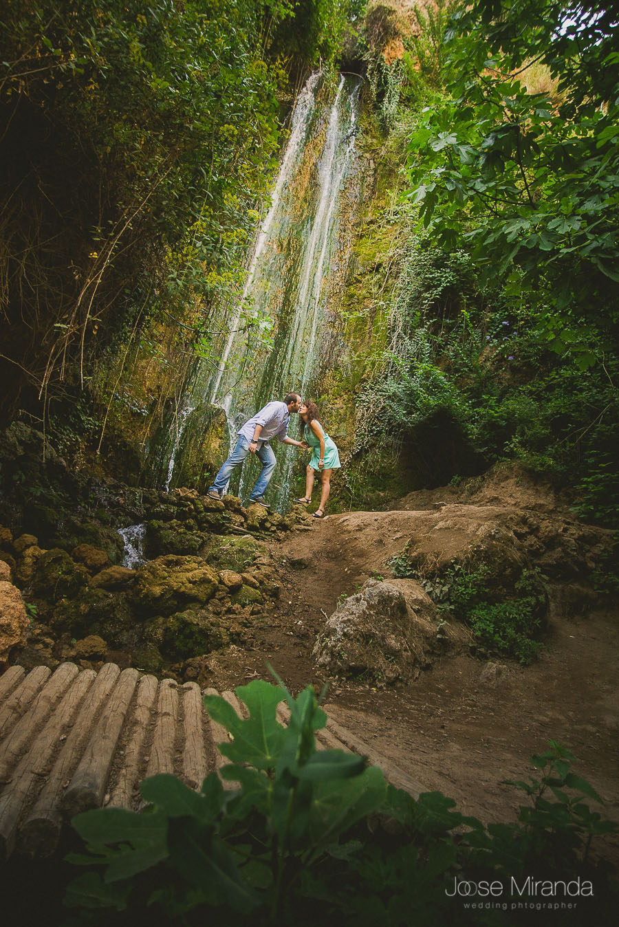 Virginia y Fran dandose un beso con la cascada de agua del rio de Valdepeñas de Jaén