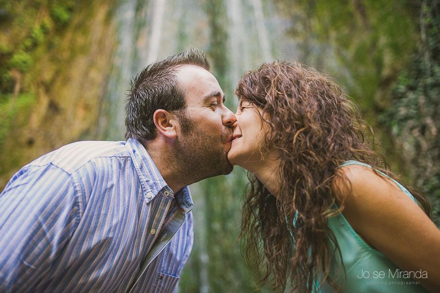 Virginia y Fran dandose un beso y una risa con una cascada de agua detrás fotografia tomada en Valdepeñas de Jaén