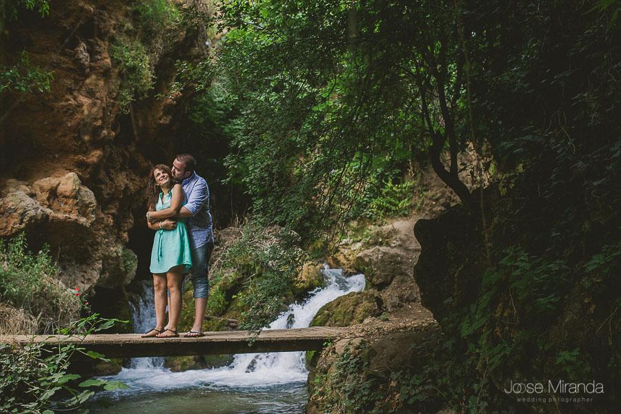Virginia y Fran abrazados en una pasarela sobre el rio de Valdepeñas de Jaén