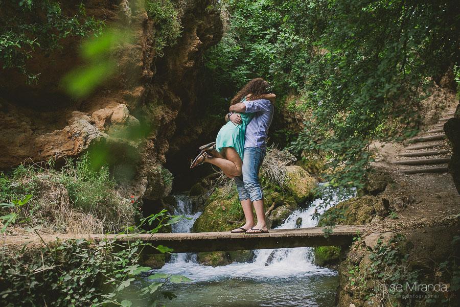 novios abrazados y saltando sobre una plataforma de un rio de Valdepeñas de Jaén