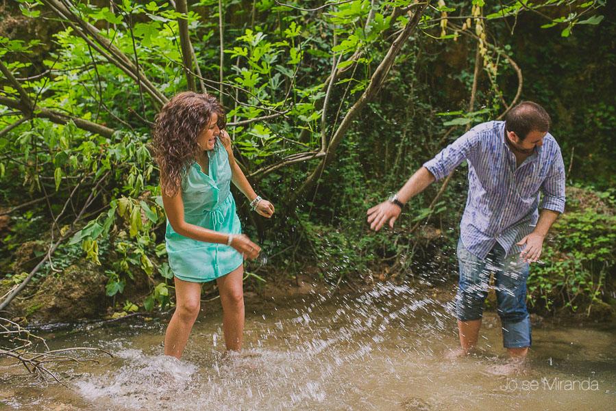 Virginia y Fran tirandose agua mientras juegan dentro del rio rodeados de vegetación en Jaén