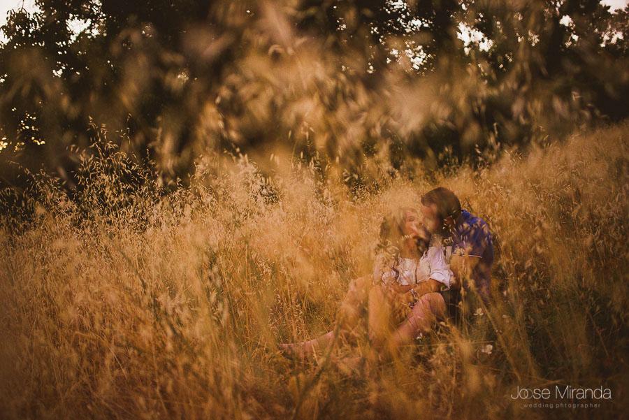 Virginia y Fran besandos entre las hierbas secas durante la sesión de fotografías de pre-boda