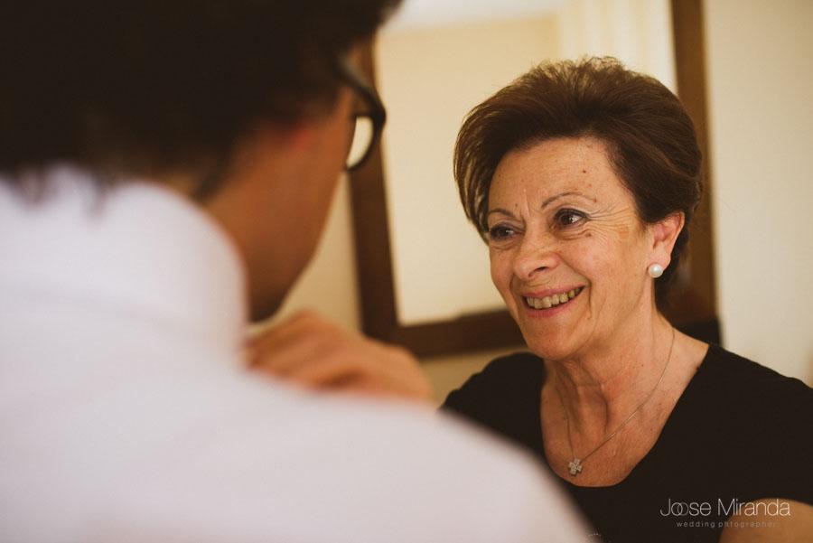 madre emocionada ayundando a vertir a su hijo el dia de la boda