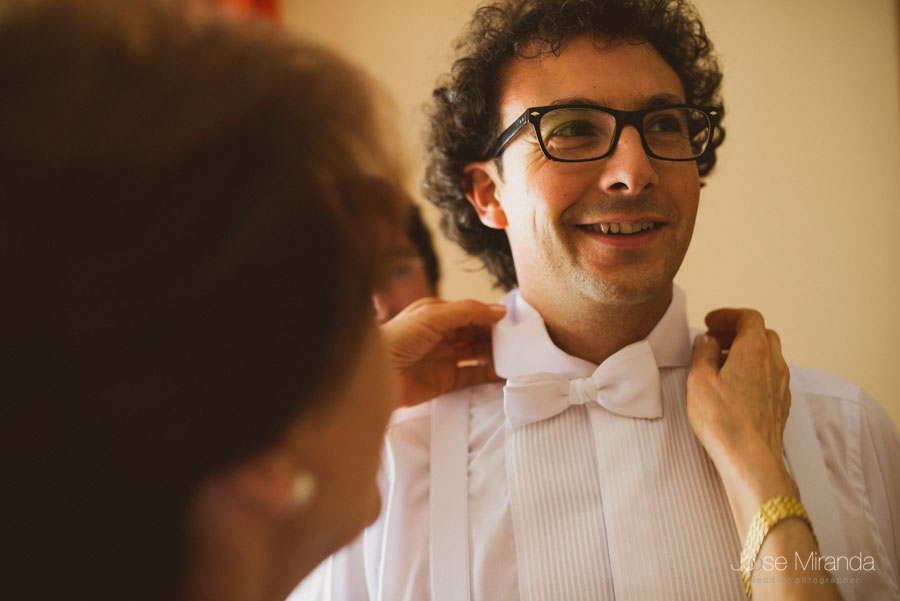 retrato de novio con pajarita blanca y camisa plisada