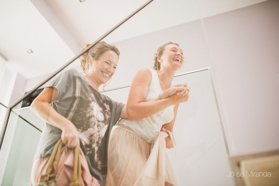 Novia y amiga riendo durante los preparativos de la boda
