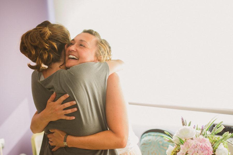 Abrazo de amiga y novia durante los preparativos de boda