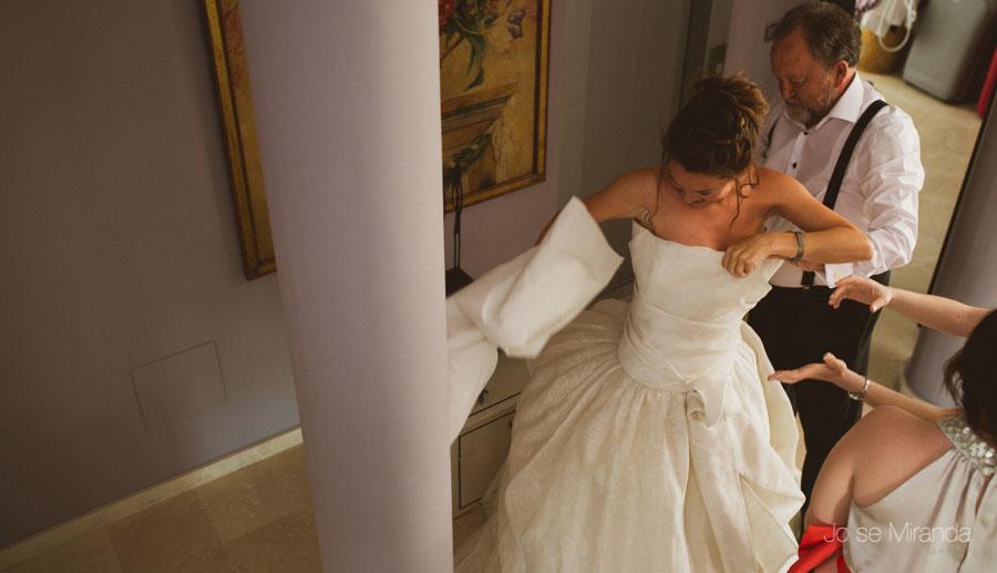 Padre de la novia ayudando a la novia a vestirse en el día de su boda en Martos
