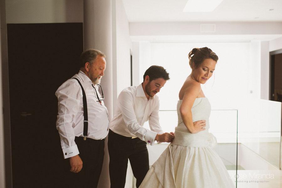 Padre de la novia y hermano de la novia abrochando los botones del vestido de Jesús Peiró