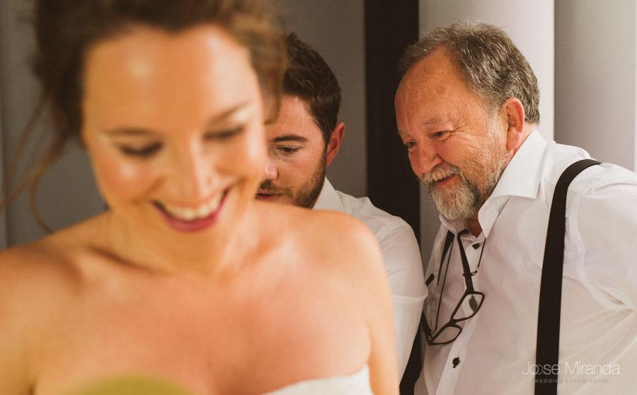 la novia ayudada por su padre y hermano a vestirse