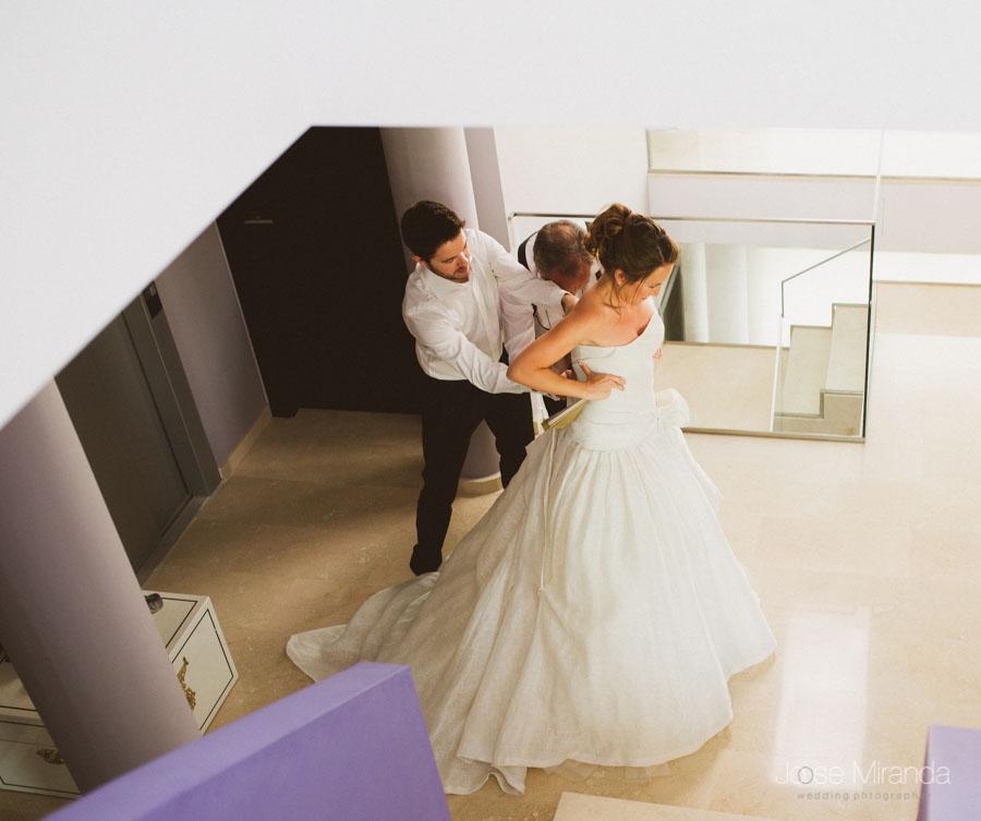 fotografía de novia vistiéndose al pie de la escalera